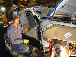 Mike George repairing crash damage to a Porsche Cayman